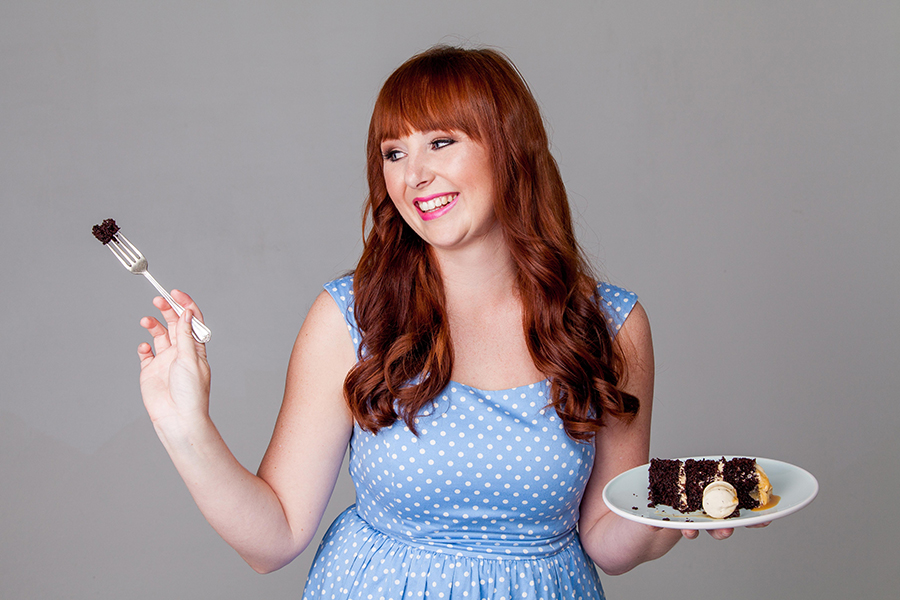Image of Katelyn Williams from The Kate Tin YouTube Channel wearing a blue polka dot dress eyeing a forkful of cake with a plate of chocolate cake in her hand